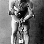 Harry Houdini (Budapest, Hungría; 24 marzo 1874 - Detroit, Míchigan, Estados Unidos; 31 octubre 1926) en 1899. Fue un ilusionista y escapista austrohúngaro nacionalizado estadounidense que concibió la magia como un espectáculo en sí mismo y demostró gran habilidad para liberarse del interior de cajas fuertes arrojadas al mar, de camisas de fuerza colgado boca abajo de rascacielos, y de toda suerte de esposas, gruesas cuerdas que le impedían mover manos y pies, baúles cerrados con candados y cadenas de cualquier tipo.
