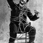 """Aunque comenzó su carrera como mago ingenioso, ocurrente y divertido haciendo juegos de cartas y otros efectos, pronto pasó a considerar practicar el escapismo. En aquella época algunos espiritistas invocaban a fantasmas mientras permanecían atados, para evitar sospechas de fraude ante los ojos de los demás. Houdini comprendió que en verdad se liberaban secretamente para manipular la escena falsamente con efectos mágicos, asegurando eran reales. Tal vez """"escaparse"""" podía ser un número en sí mismo."""