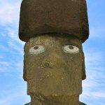 """Moái de la plataforma Ahu Tahai luciendo el """"pukao"""", especie de cilindro de piedra rojiza de entre uno y dos metros de alto, por dos a tres metros de diámetro, situado como ornamento sobre la cabeza de las estatuas que representa los moños rojos típicos de los habitantes originales de la isla. Están elaborados con la escoria roja (ceniza de gran porosidad y escasa dureza) extraída del volcán Puna Pau, llegando a pesar el más voluminoso 11 toneladas. Su número no alcanza el centenar aunque es posible que haya más piezas enterradas por los caminos o incorporadas como material de construcción reciclado a las propias plataformas ceremoniales (""""ahu"""")."""