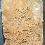 Representación de Ek Chuah (dios del comercio), labrado en un ladrillo descubierto en Comalcalco. El viaje comercial en territorio extranjero peligroso se comparó con un pasaje por el inframundo. Cuando los comerciantes salían, iban fuertemente armados y pintados de negro, al igual que sus deidades patronas.